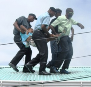 The Teen being taken off the roof. [iNews' Photo]