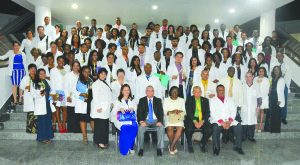 Public Health Minister, Dr George Norton; Minister within the Ministry of Public Health, Dr Karen Cummings and the Cuban Ambassador to Guyana, Julio César González Marchante with the 86 new doctors at the Arthur Chung Convention Centre