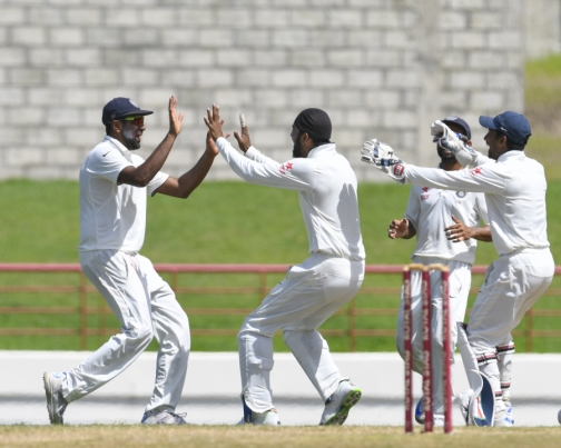 Ravichandran Ashwin (L) and Lokesh Rahul (R) of India celebrate the dismissal of Jason Holder of West Indies on the 5th and final day of the 3rd Test between West Indies and India at Darren Sammy National Cricket Stadium in Gros Islet, St Lucia. (Photo: AFP)