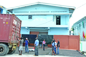 Workers outside of the Linden Holding Inc 'drug bond' on Sussex Street, Albouystown on Thursday