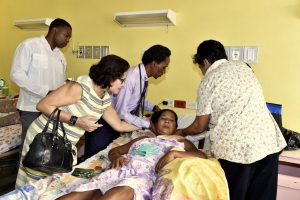 First Lady, Mrs. Sandra Granger helps the attending physician and another visitor to ease Ms. Ophelia James into a more comfortable position on her bed at the Georgetown Public Hospital Corporation.