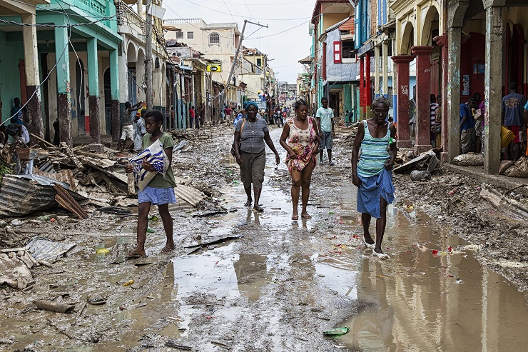 People walk along a street in downtown Jeremie Haiti, Thursday October 6, 2016. Hurricane Matthew passed over Haiti on Tuesday October 4, 2016, with heavy rains and winds. While the capital Port au Prince was mostly spared from the full strength of the class 4 hurricane, the western cities of Les Cayes and Jeremie received the full force sustaining wind and water damage across wide areas.  Photo Logan Abassi UN/MINUSTAH