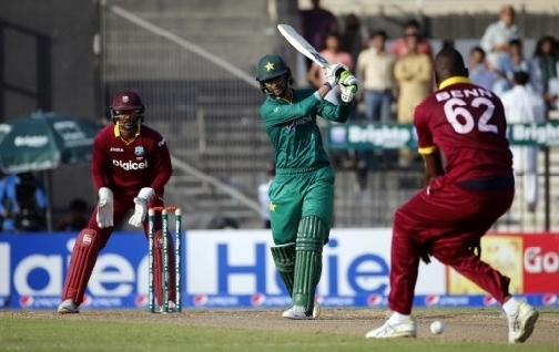 Pakistan's batsman Shoaib Malik (C) hits the ball as West Indies' wicketkeeper Densh Ramdin (L) fields during the 2nd ODI match between Pakistan and West Indies at the Sharjah Cricket Stadium, on October 2, 2016. (Photo: AFP)