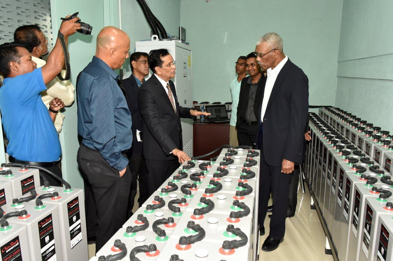 President David Granger takes a look at some of the batteries, which are a part of the solar electricity system at Demerara Bank Limited, as CEO, Mr Pravinchandra Dave explains how the system works