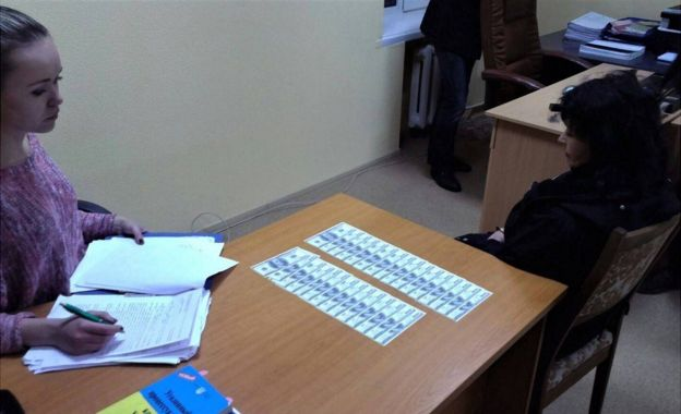 The teacher (right) is shown here being questioned, with US dollars spread out on the table (Arsen Avakov image)