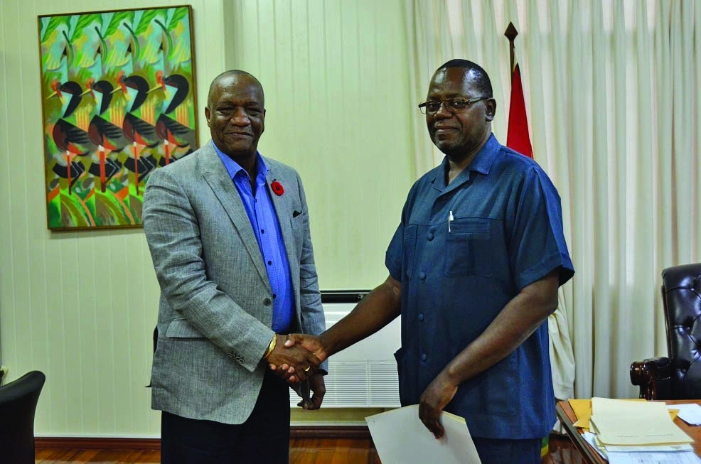Retired Assistant Commissioner of Police, Winston Cosbert being presented with the Terms of Reference (TORs) by Minister of State, Joseph Harmon