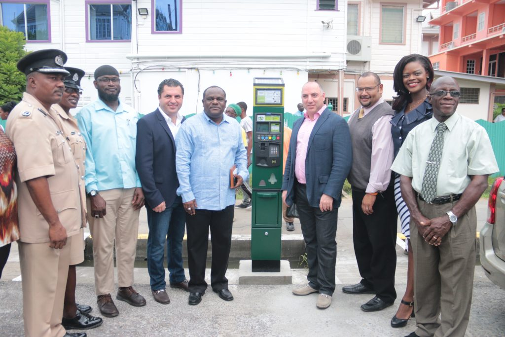 Managing Director of Smart City Solutions, Amir Oren,(3rd left) Town Clerk Royston King and other representatives flank the installed meter (Marciano Narine photo)